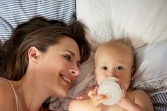 Retrato de uma mãe feliz com o bebê bonito que bebe da garrafa fotografia de stock