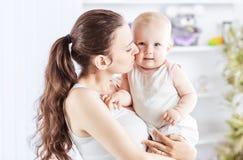 Retrato de uma mãe feliz com um bebê dos anos de idade em seus braços no fundo de uma sala do ` s da criança Imagem de Stock Royalty Free