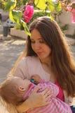 Retrato de uma mãe feliz que guarda a filha de sono em seus braços Foto de Stock Royalty Free