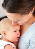 Retrato de uma mãe que guarda o bebê perto da caixa Fotos de Stock Royalty Free