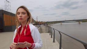 Retrato de uma m?sica de escuta da menina feliz em fones de ouvido de um smartphone na rua em um dia ensolarado do ver?o filme