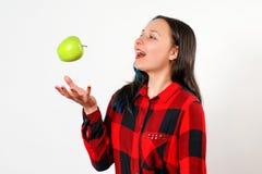 Retrato de uma maçã de jogo de sorriso da menina feliz no ar no fundo branco fotografia de stock