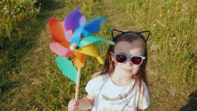 Retrato de uma menina à moda com um moinho de vento do brinquedo em suas mãos filme