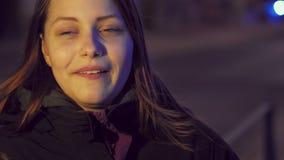 Retrato de uma menina adolescente de sorriso pensativa bonito em uma rua da cidade da noite slowmo de 4K UHD video estoque