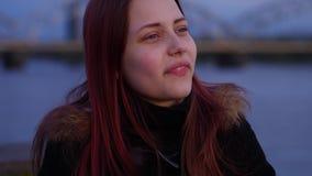 Retrato de uma menina adolescente de sorriso pensativa bonito em uma rua da cidade da noite slowmo de 4K UHD filme