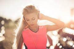 Retrato de uma menina adolescente desportiva que descansa do exercício, usando a escuta a música com os fones de ouvido, sorrindo Imagem de Stock