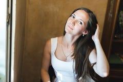 Retrato de uma menina agradável que fixa seu cabelo imagens de stock royalty free
