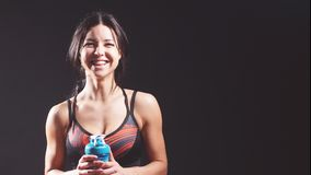 Retrato de uma menina alegre atlética no estúdio em um fundo preto com uma garrafa da água video estoque