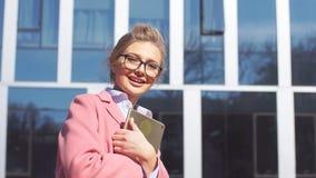 Retrato de uma menina alegre do negócio com a tabuleta no fundo de um prédio de escritórios moderno filme