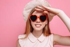 Retrato de uma menina alegre em um chapéu do verão e em uns óculos de sol coração-dados forma que esperam umas férias imagem de stock royalty free