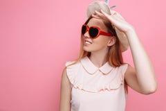 Retrato de uma menina alegre em um chapéu do verão e em uns óculos de sol coração-dados forma que esperam umas férias imagens de stock