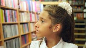 Retrato de uma menina 8 - 12 anos velha, posição na biblioteca Estantes de uma biblioteca no fundo 4k, lento video estoque