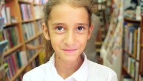 Retrato de uma menina 8 - 12 anos velha, posição na biblioteca Estantes de uma biblioteca no fundo 4k, lento vídeos de arquivo