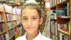 Retrato de uma menina 8 - 12 anos velha, posição na biblioteca Estantes de uma biblioteca no fundo 4k, lento filme