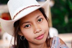 Retrato de uma menina asiática bonita com o chapéu branco que refrigera para fora durante a noite na praia Foto de Stock