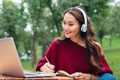 Retrato de uma menina asiática de sorriso feliz nos fones de ouvido foto de stock royalty free