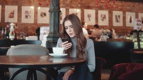 Retrato de uma menina atrativa em um café Reescritas de uma menina em um smartphone que senta-se em uma tabela em uma casa do caf video estoque