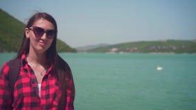 Retrato de uma menina atrativa nova em uma camisa quadriculado vermelha, levantando na frente da câmera filme