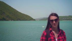 Retrato de uma menina atrativa nova em uma camisa quadriculado vermelha, levantando na frente da câmera vídeos de arquivo
