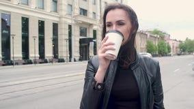Retrato de uma menina atrativa nova em um casaco de cabedal preto estar no vento frio e no café bebendo de um copo de papel cit video estoque