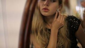 Retrato de uma menina bem arrumado bonita que tenta na joia na frente do espelho Mulher bonita que tenta em brincos video estoque