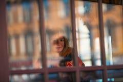 Retrato de uma menina bonita através da janela de vidro com brilho imagens de stock