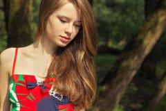 Retrato de uma menina bonita com cabelo vermelho com bordos gordos em um vestido vermelho em um dia de verão na rua Fotos de Stock