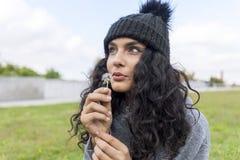 Retrato de uma menina bonita com flor do dente-de-leão imagens de stock royalty free