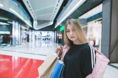 Retrato de uma menina bonita com os sacos de compras nas mãos de um shopping Conceito da compra imagens de stock royalty free