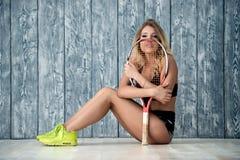 Retrato de uma menina bonita da menina com uma raquete, um fundo cinzento da parede de tijolo imagens de stock royalty free