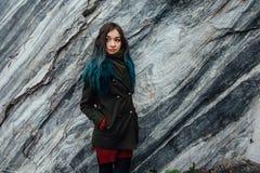 Retrato de uma menina bonita do moderno no fundo os penhascos rochosos Cabelo tingido, azul, por muito tempo Imagem de Stock