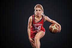 Retrato de uma menina bonita e 'sexy' com um basquetebol no estúdio Conceito do esporte isolado no fundo preto fotografia de stock