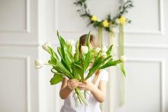 Retrato de uma menina bonita em uma camisa branca que esconde atrás de um ramalhete das tulipas brancas foto de stock