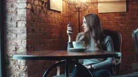 Retrato de uma menina bonita em um café a menina faz o selfie no smartphone da câmera e bebe o café vídeos de arquivo