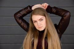 Retrato de uma menina bonita em um escuro - vestido vermelho knee-deep e em um casaco de cabedal escuro na rua no fundo da tarde imagem de stock royalty free