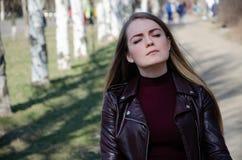 Retrato de uma menina bonita em um escuro - vestido vermelho knee-deep e em um casaco de cabedal escuro na rua no fundo da tarde imagem de stock