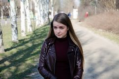 Retrato de uma menina bonita em um escuro - vestido vermelho knee-deep e em um casaco de cabedal escuro na rua no fundo da tarde fotografia de stock