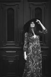 Retrato de uma menina bonita em um vestido com um chapéu na porta Imagem de Stock Royalty Free