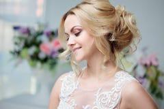 Retrato de uma menina bonita em um vestido de casamento Noiva em um vestido luxuoso em um fundo branco, penteado bonito foto de stock