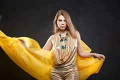Retrato de uma menina bonita em um vestido do ouro Fotos de Stock Royalty Free