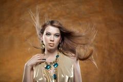 Retrato de uma menina bonita em um vestido do ouro Imagem de Stock Royalty Free