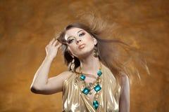 Retrato de uma menina bonita em um vestido do ouro imagens de stock