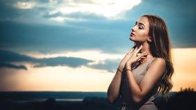 Retrato de uma menina bonita na perspectiva de um céu nebuloso no por do sol, uma jovem mulher da noite em um vestido res do verã fotos de stock royalty free
