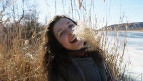 Retrato de uma menina bonita no banco de um rio congelado que aprecia a natureza, rindo e jogando com bastão amarelo vídeos de arquivo