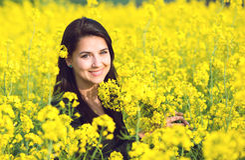 Retrato de uma menina bonita no campo da couve-nabiça no verão imagem de stock royalty free