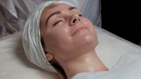 Retrato de uma menina bonita no procedimento no salão de beleza Close-up Um cosmetologist-terapeuta aplica vídeos de arquivo