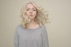 Retrato de uma menina bonita nova com voo luxuoso do cabelo no fundo claro Fotografia de Stock