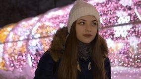 Retrato de uma menina bonita nova No inverno na noite Aquece suas mãos nos mitenes Movimento lento vídeos de arquivo