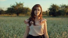 Retrato de uma menina bonita que anda no campo A menina move-se longe da câmera e dos sorrisos vídeos de arquivo