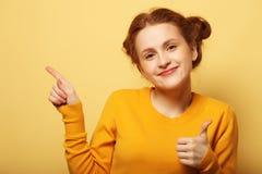 Retrato de uma menina bonita que aponta o dedo afastado sobre o CCB amarelo foto de stock